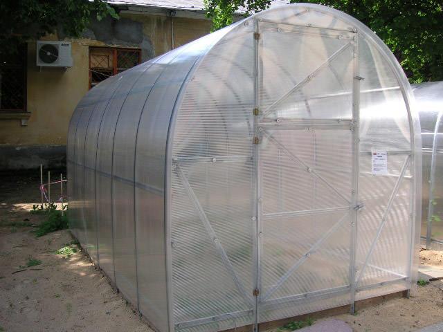 Теплица «Эконом» в отличие от «Урожай ПК» отличается тем, что арочная форма в данном случае присутствует только у крыши. Каркас имеет V-образную форму